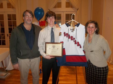 Noah Schultz (middle) holding his Hobey Baker plaque with his mom, Rebecca Schultz and his dad, Dan Schultz.