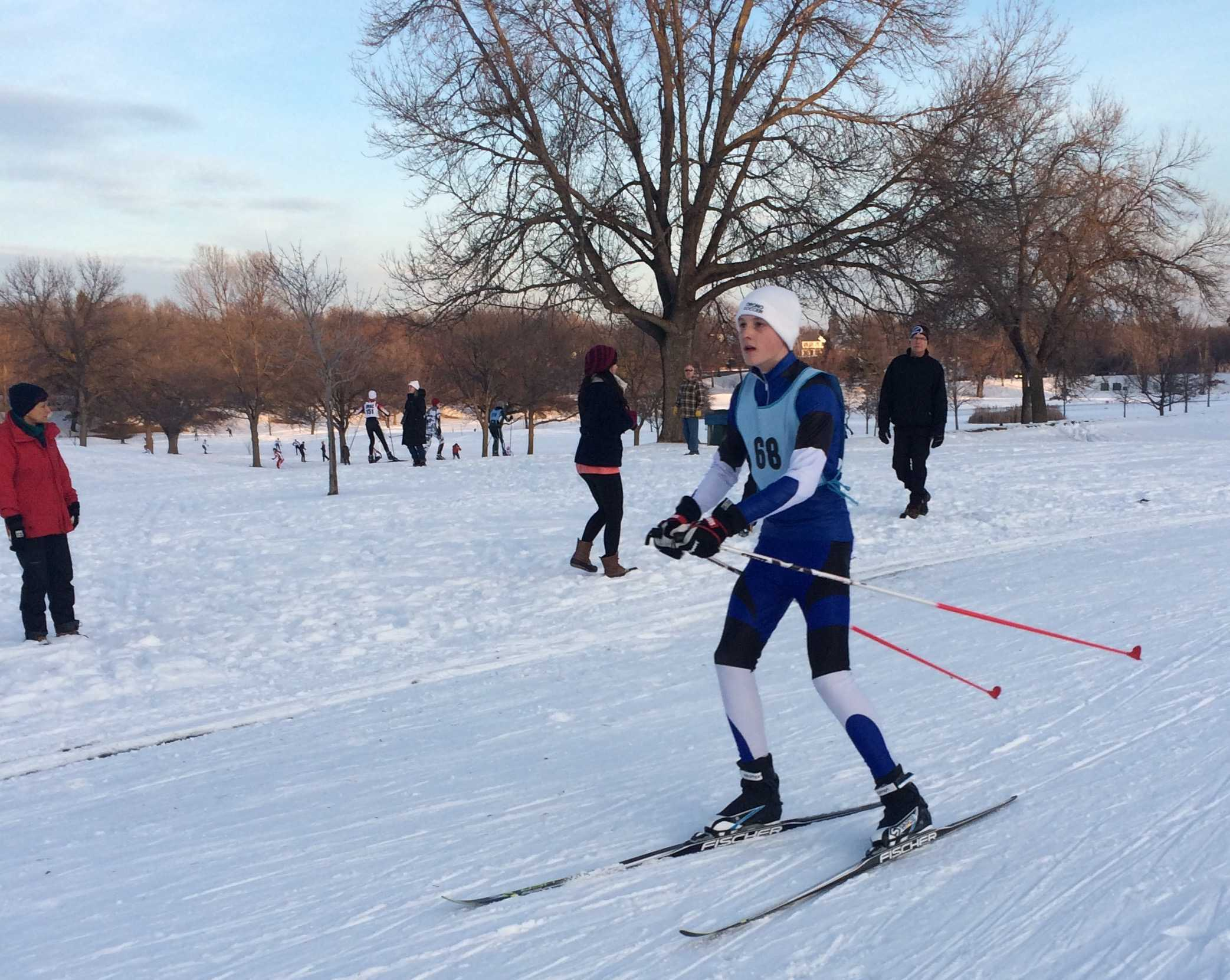 Photo/ Ella Langer  Varsity skier juniot Connor Hasselman skies hard as he races toward the finish line, completing the 8K course strong.