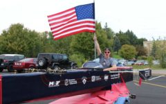 Senior Carver Squiers holds up the American flag at the 2016 Homecoming Parade