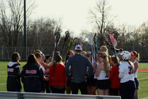 The girls lacrosse team huddles together.