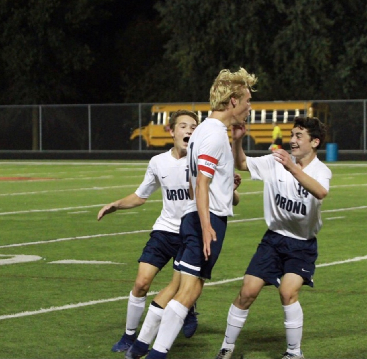 Christian Babo (middle) celebrates goal with teammates Ozzie Ramsey (left) and Jamie Bazil (right).
