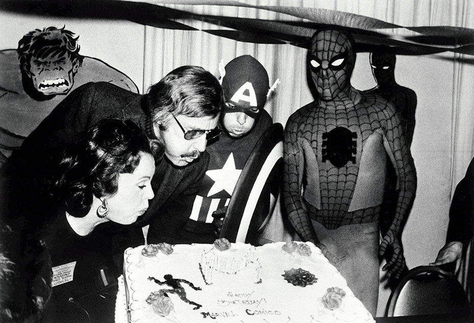 Marvel comic book publisher, Stan Lee (center left), blows out the candles on the Marvel Comics birthday cake at opening day ceremonies of the First Mighty Marvel Comic Book Convention, Mar. 22, 1975, New York. To the left is Lee's wife Joan and on the far right, Spider-Man. Another Marvel superhero, Captain America helps blow out the candles.