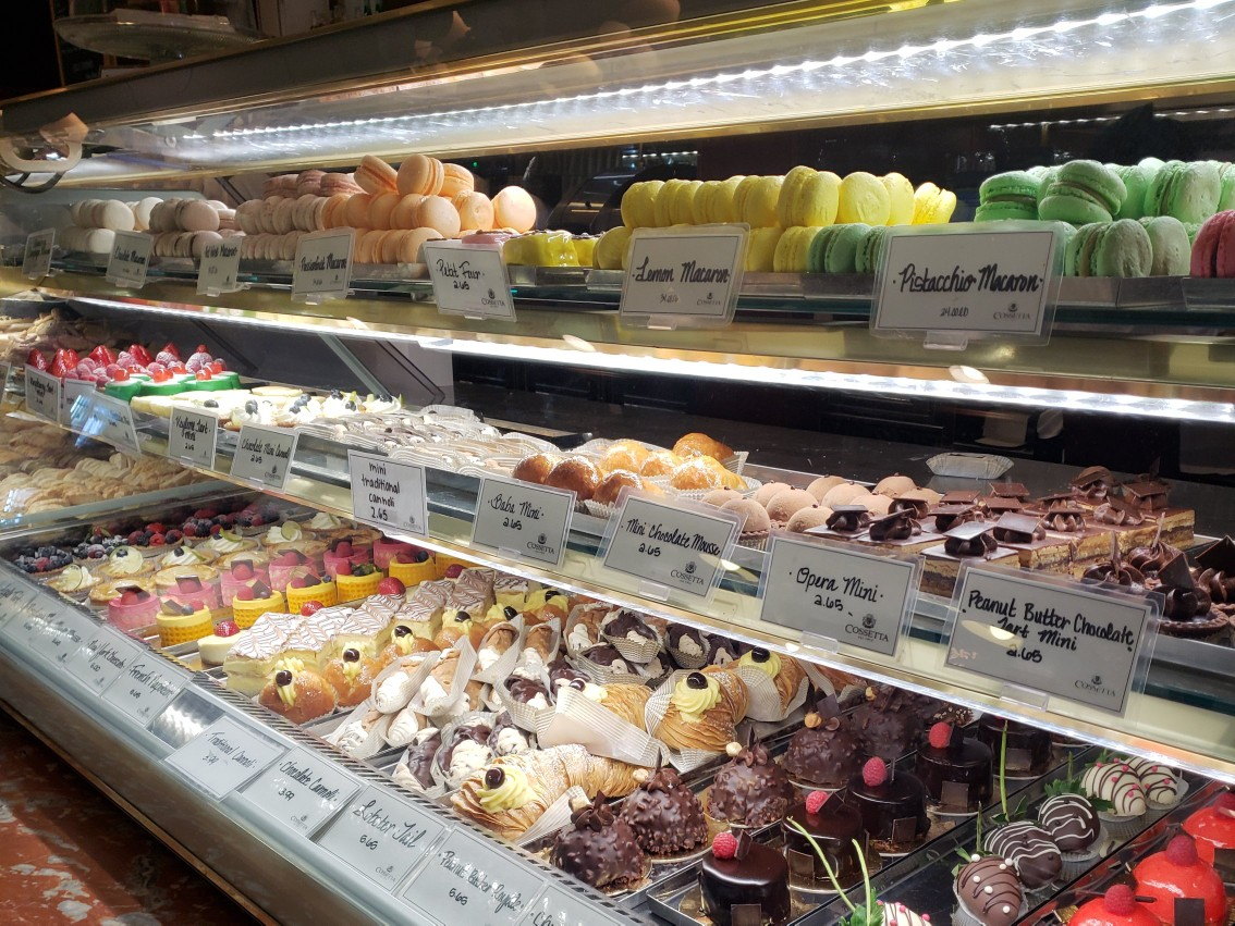 A display case full of ornately decorated pastries offered in Cossetta's pasticceria.