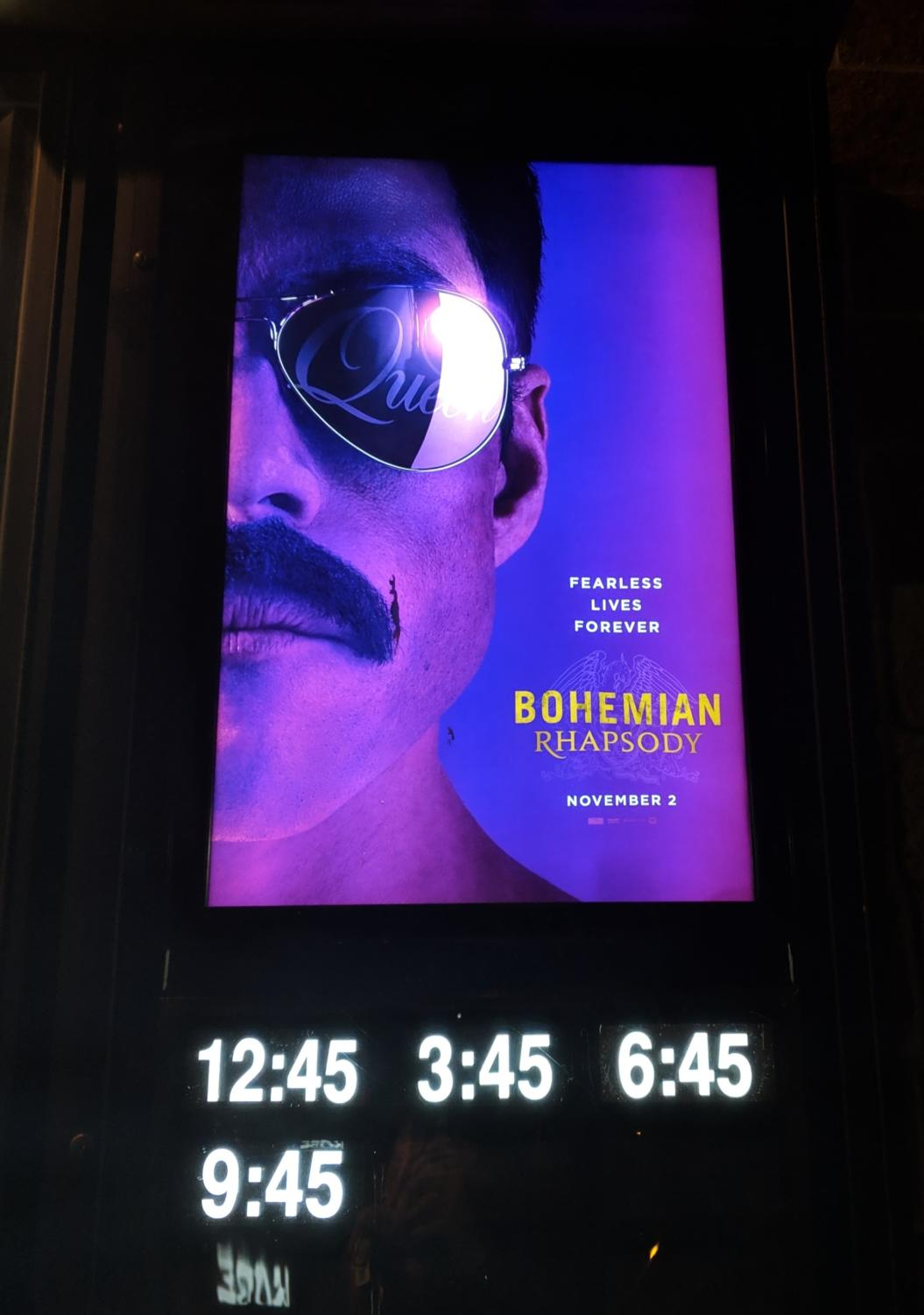 The movie poster that is outside of the theater.