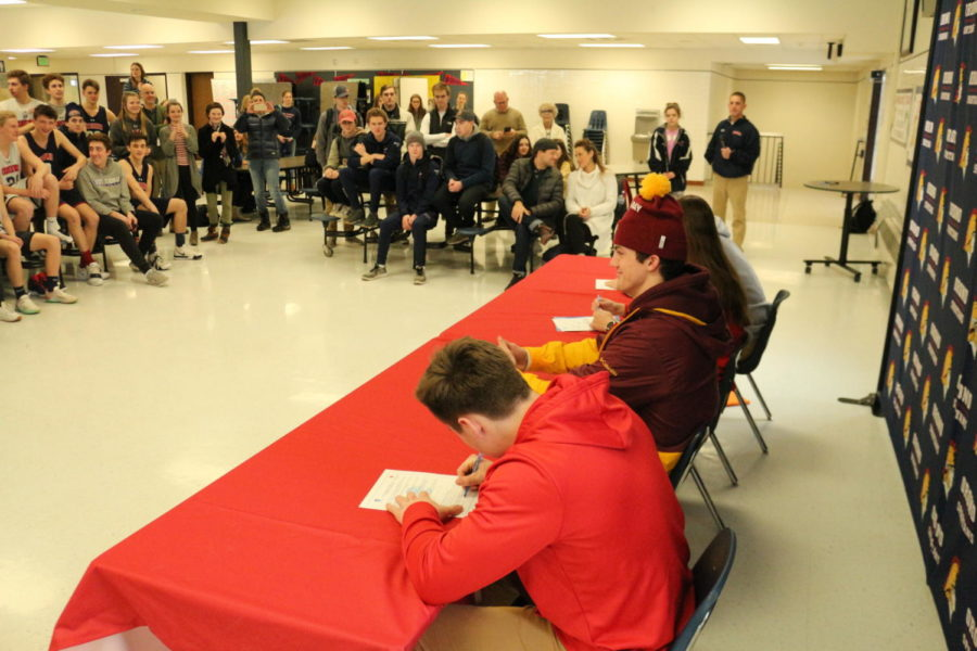 Friends+and+Family+watch+as+student+athletes+sign+their+letters+of+intent