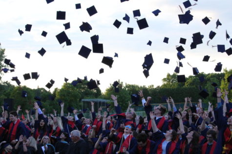 Students throw their caps in the air to celebrate their graduation.