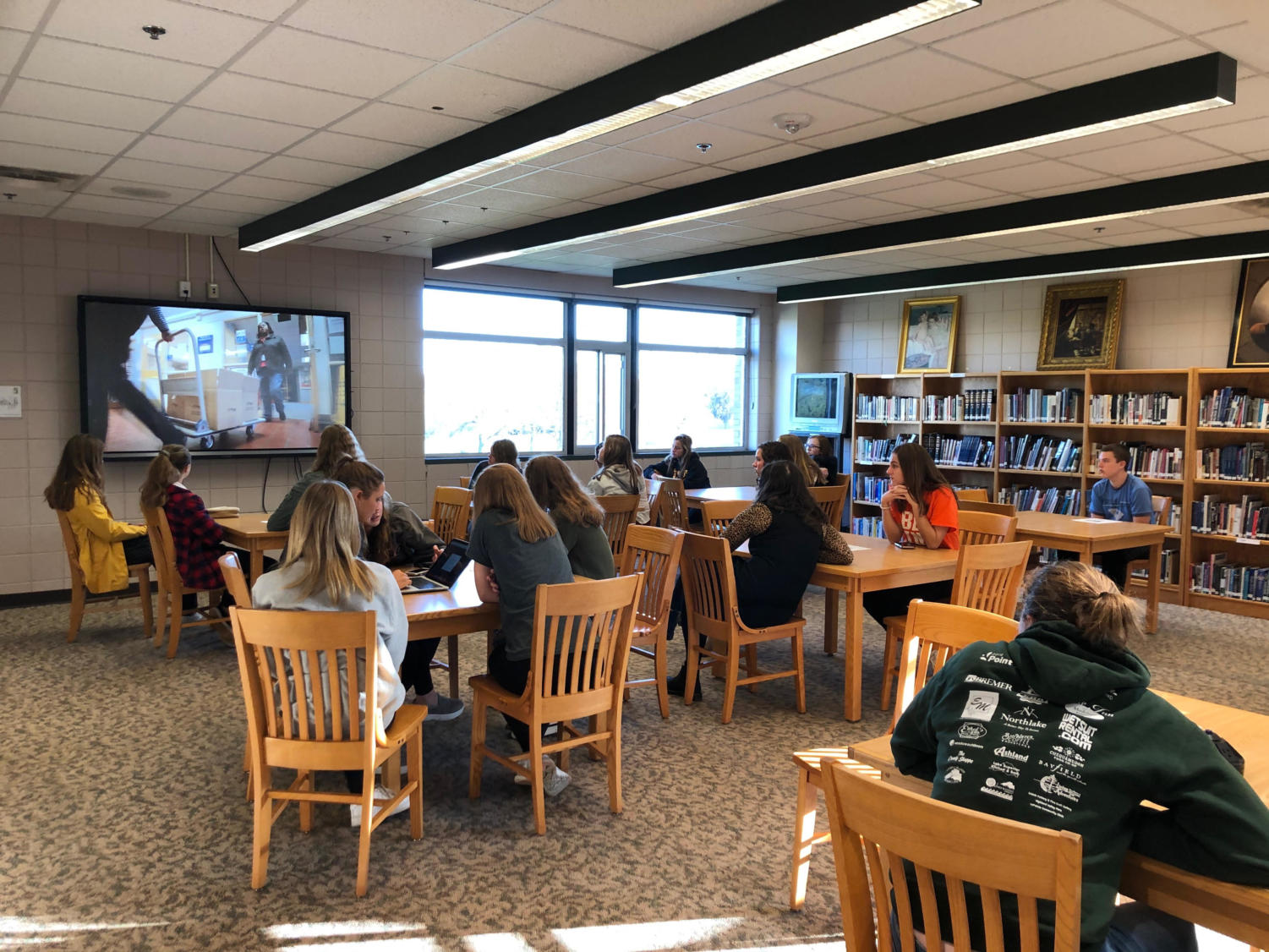 Youth in Action prepares for their upcoming food drive by watching an educational video.