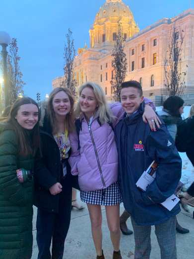 Delegates Emma Davie, Claire Suchy, Nina Johnson, and Blake Ament stand outside the Capitol Building.