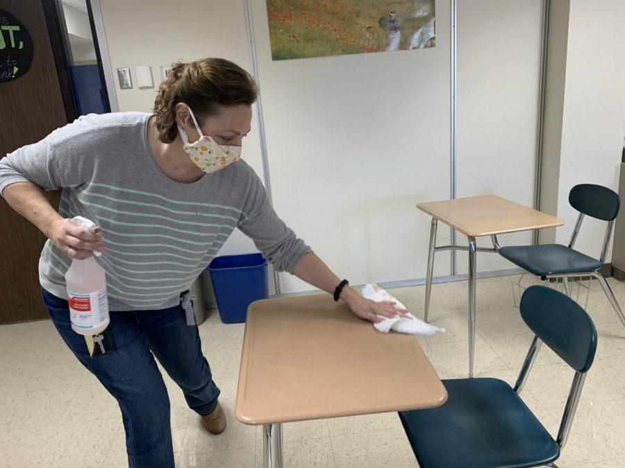 Mrs. Herring sanitizes desks between classes.