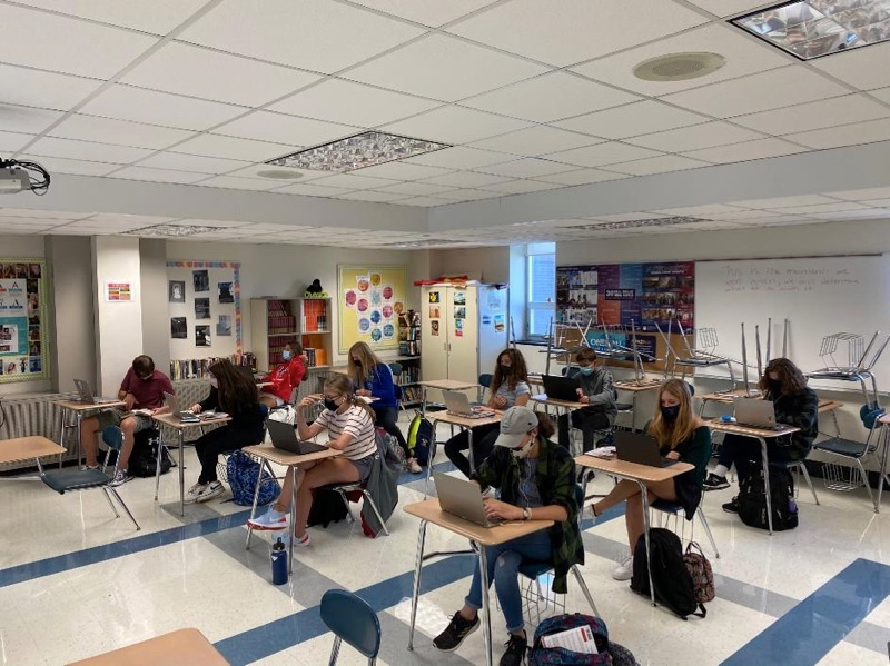 Students in a classroom complete work on their laptops.