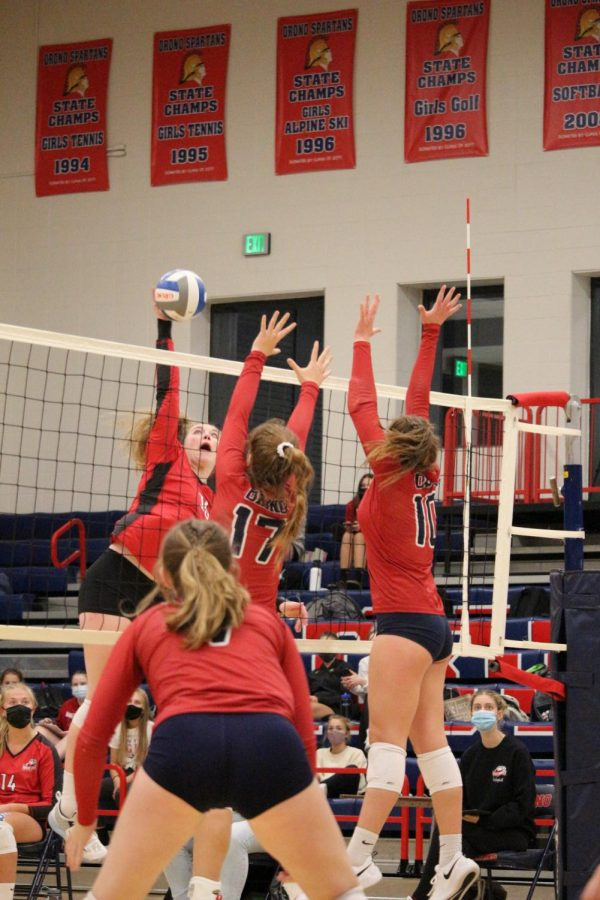 At Orono High School on November 5, Girls Varsity Volleyball plays a game against Mound Westonka High School. Freshman Izzy Torve (10) and Junior Sophie Jaques (17) block the opponent, which teammate Lily Maas (7) is covering.