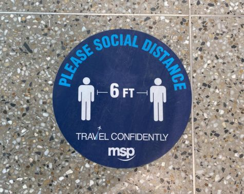 "MSP Airport encourages people to ""travel confidently"" on their signs by promoting social distancing."