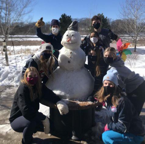 Orono students gather around the snowman they made outside the windows at the Trails of Orono.
