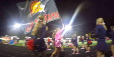 Megan Kostial runs through the Orono Cheerleaders waving the Spartans flag to rev. up the crowd.